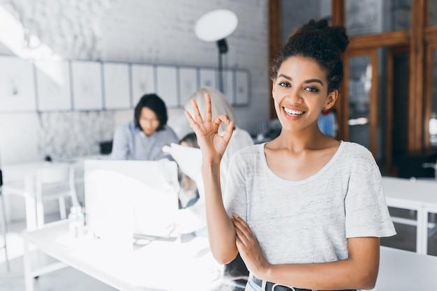 Estudiante mulata rizada posando con sonrisa y signo bien después de una prueba difícil en la universidad internacional. retrato interior de mujer africana trabaja como gerente en la oficina con un joven asiático detrás.