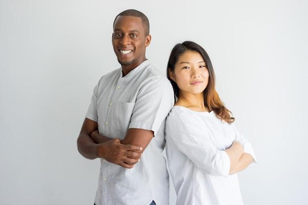 Estudiante multiétnico joven confiado alegre que se coloca de nuevo a la parte posterior y que mira la cámara