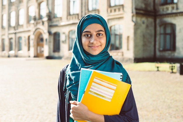 Estudiante musulmán joven sonriente que sostiene los libros que se colocan cerca de universidad. feliz niña árabe en hijab. mujer asiática en formación.