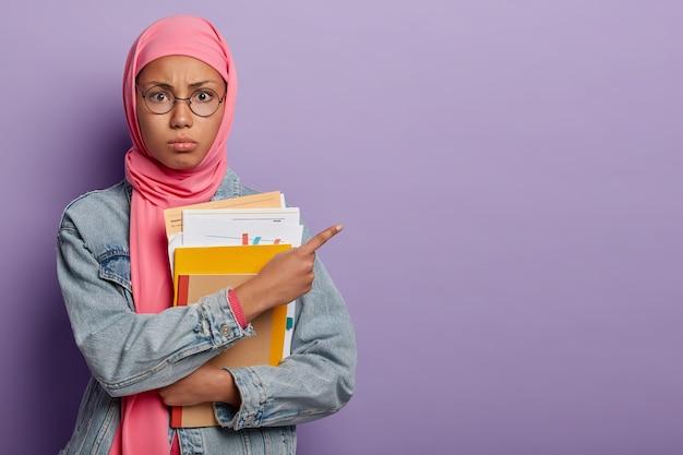 Estudiante musulmana adolescente posa con papeles y libros de texto, apunta a un lado en el espacio libre, lleva gafas ópticas redondas y hijab rosa