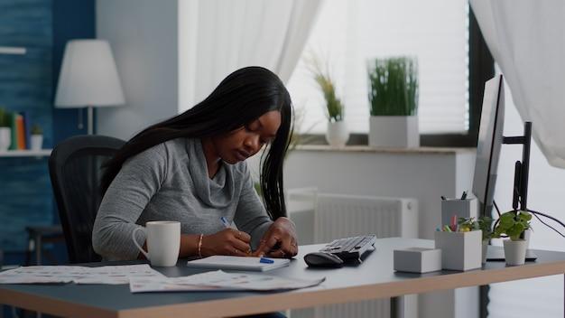 Estudiante negro escribiendo ideas de educación en notas stickey sentado en la mesa de escritorio en la sala de estar