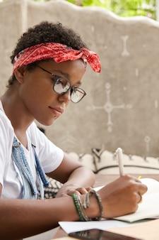 Estudiante negro internacional trabaja en informe.