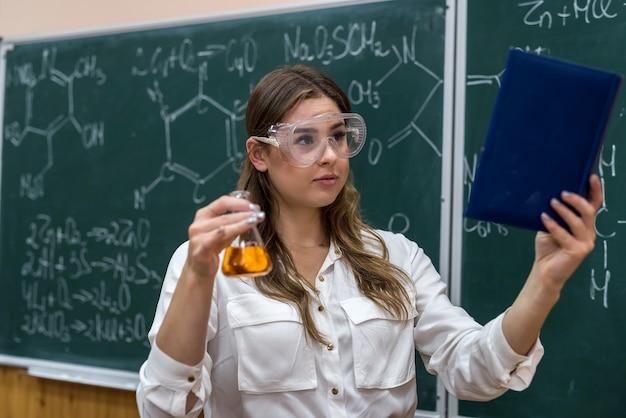 Estudiante niña realiza un experimento en la lección de química sosteniendo líquido de color en un matraz en la pizarra
