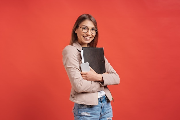 Estudiante o pasante sonriente joven en las lentes que se colocan con una carpeta en la pared roja.