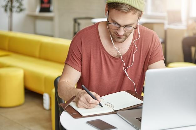 Estudiante ocupado lleva gafas redondas y sombrero, escribe notas en el cuaderno,