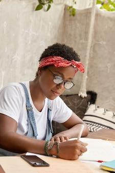 Estudiante ocupado se prepara para un seminario universitario, escribe tesis, hace tareas en casa