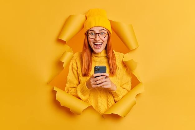 Una estudiante pelirroja emocionada emocional utiliza un teléfono móvil moderno para enviar mensajes de texto, chats en línea con sus compañeros de grupo, oye noticias excelentes y usa ropa amarilla