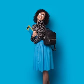 Estudiante de pelo rizado con anteojos y bolsa sosteniendo algunas carpetas