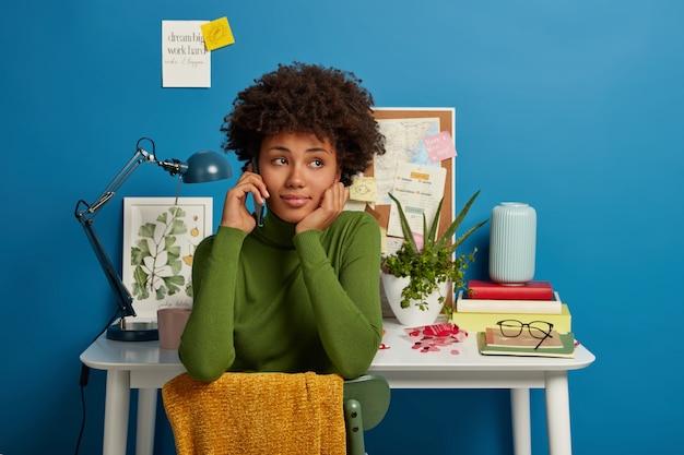 Una estudiante pensativa de cabello rizado llama a un compañero de grupo a través de un teléfono inteligente, se sienta en una silla en su propia sala de estudio, una mesa con lámpara de escritorio y blocs de notas, notas adhesivas en la pared con información escrita
