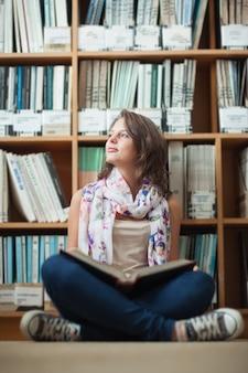 Estudiante pensativa contra la estantería con un libro en el piso de la biblioteca