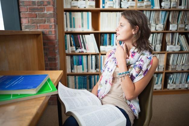Estudiante pensativo con un libro en la biblioteca