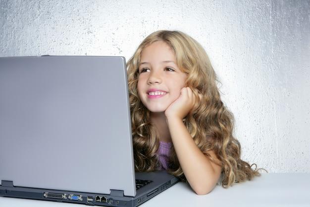 Estudiante pequeña colegiala en computadora portátil