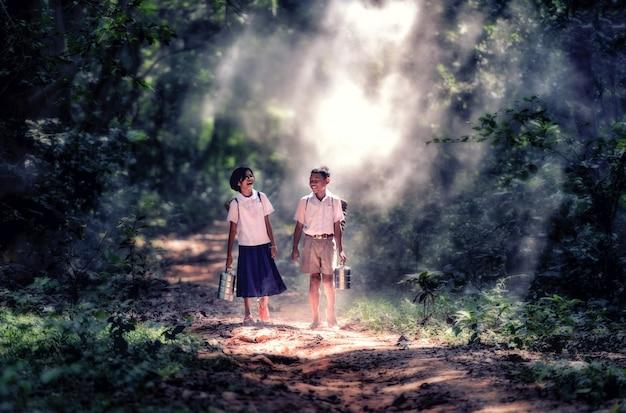 Estudiante pequeño muchacho y muchacha asiáticos, campo en tailandia