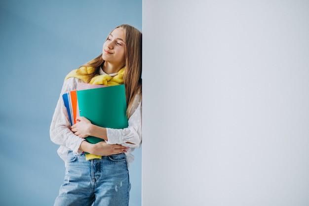 Estudiante de pie con carpetas coloridas