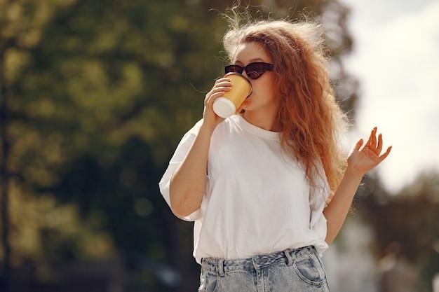 Estudiante de pie en una ciudad con una taza de café