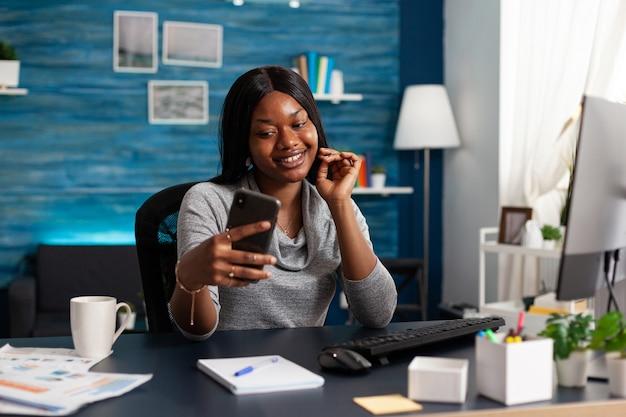 Estudiante con piel oscura discutiendo el curso de comunicación con un colega remoto durante una videollamada en línea