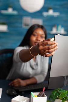 Estudiante con piel oscura poniendo notas stickey en computadora estudiando lección de comunicación