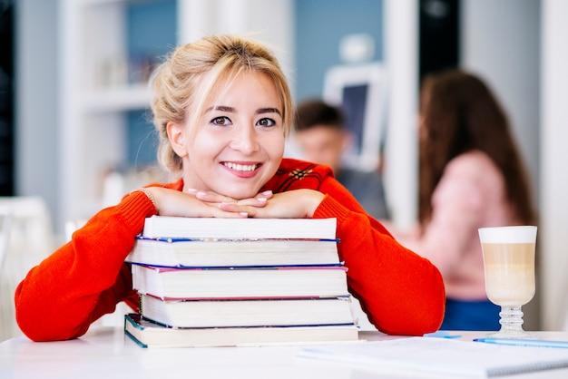 Estudiante con pila de libros sobre la mesa