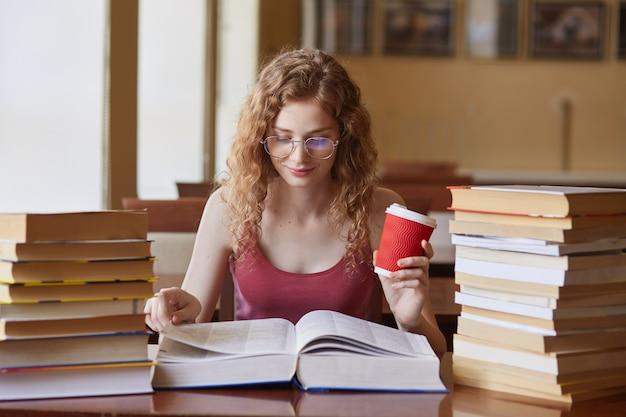 Estudiante posando con café en la mano, adornada con pilas de libros en la sala de reding. mujer joven sentada en la mesa haciendo tareas en la biblioteca de la universidad, preparándose para las clases concepto de educación
