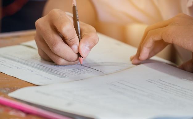 Estudiante de pregrado escribiendo lápiz en cuestionarios de opción múltiple
