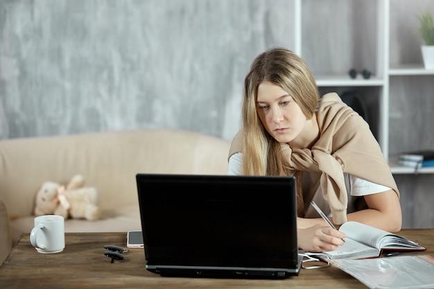 Un estudiante se está preparando para las pruebas de verificación, sentado en una mesa con una computadora portátil