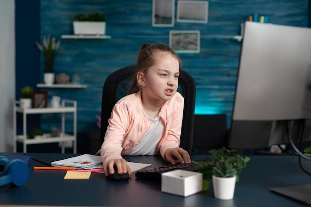 Estudiante de primaria cansado que se une a la lección en línea desde casa