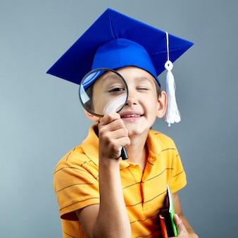 Estudiante de primaria con lupa y gorro de graduación