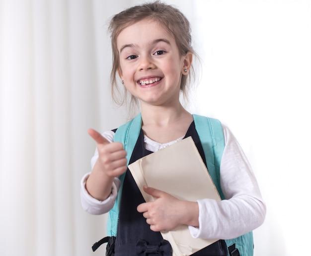 Estudiante de primaria con una mochila y un libro