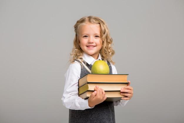 Estudiante de primer grado con libros y una manzana sonriendo sobre un fondo brillante