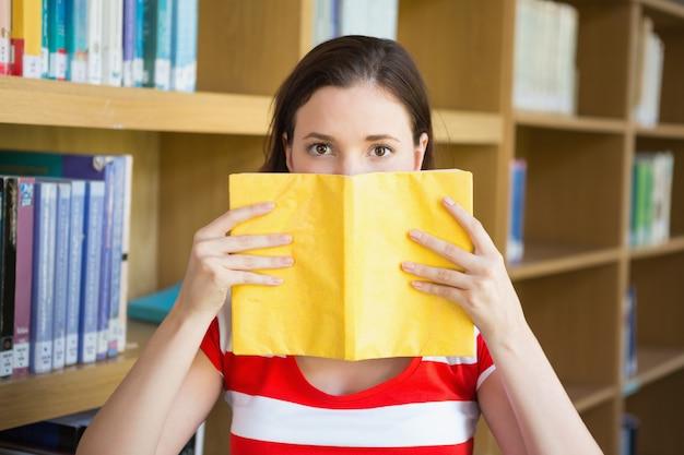 Estudiante que cubre la cara con el libro en la biblioteca