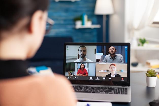 Estudiante que estudia el curso de estilo de vida con su grupo escolar durante la reunión de videollamada en línea usando una computadora portátil. mujer joven con educación remota durante cuarentena por coronavirus