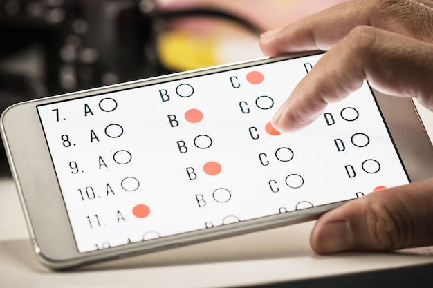 Estudiante que evalúa el aprendizaje en línea, el examen de e-learning en un teléfono inteligente con opción múltiple