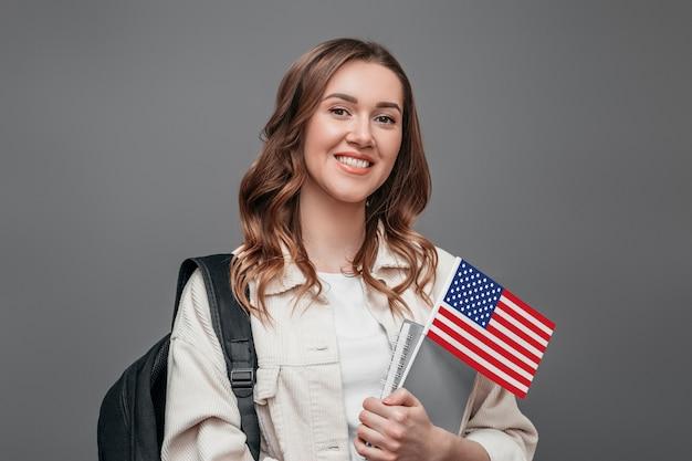 Estudiante que sonríe sosteniendo la mochila y la bandera de los eeuu aisladas en concepto gris del intercambio del estudiante de la pared. retrato de una linda chica estudiante en una pared oscura con la bandera de américa