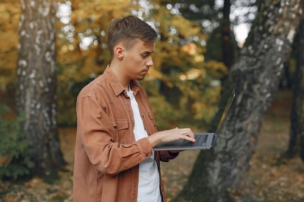 Estudiante que trabaja en un parque y usa la computadora portátil