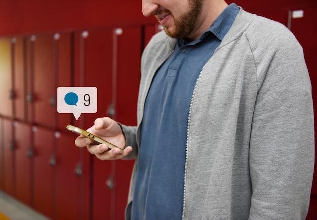 Estudiante que usa las redes sociales en su teléfono inteligente