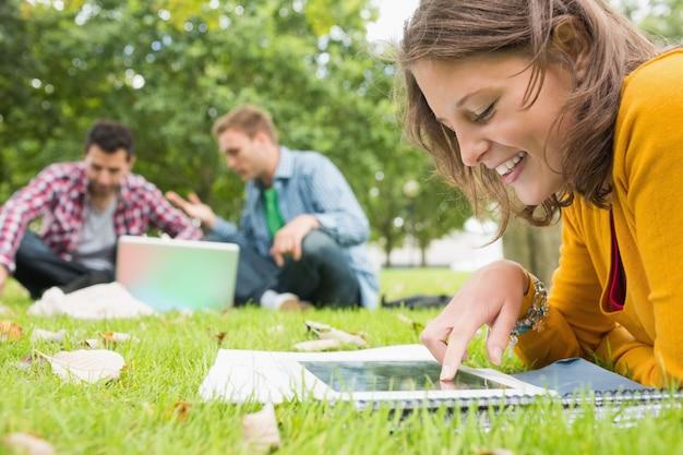 Estudiante que usa la tableta mientras que los hombres que usan la computadora portátil en el parque
