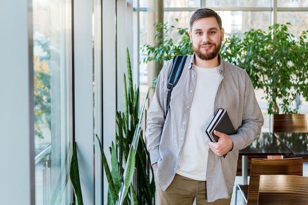 Estudiante en reabrir el pasillo del campus universitario cerca de la ventana. adolescente caucásico con libros de texto de cuadernos de mochila. hombre guapo con barba sonriente. freelancer en oficina de coworking moderna con plantas.
