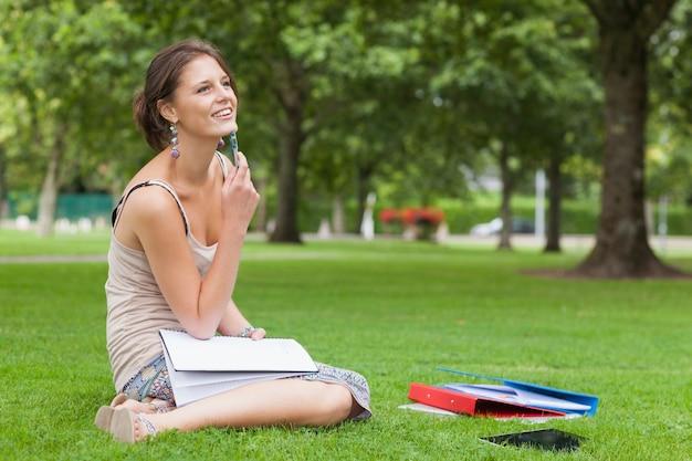 Estudiante reflexivo con libros sentado en el parque