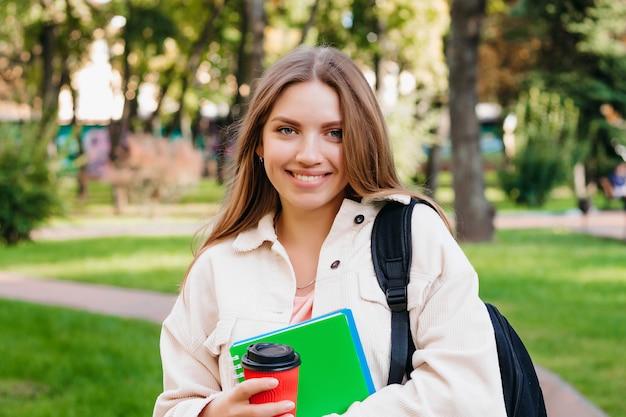 Estudiante rubia camina en el parque con un cuaderno y una taza de café, copia espacio. concepto de educación