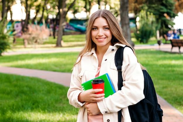 Estudiante rubia camina en el parque con un cuaderno y una taza de café