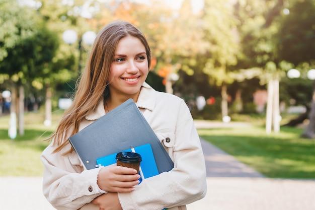 Estudiante rubia camina en el parque con cuadernos de carpetas y una taza de café
