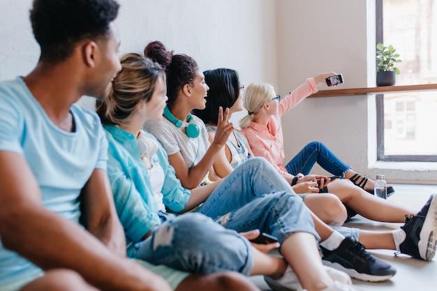 Estudiante rubia con gafas sentado junto a la ventana y haciendo selfie con compañeros de clase. retrato de amigos mirando a la chica rubia que les toma una foto.