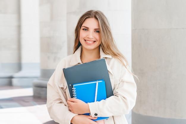 Estudiante rubia joven que sonríe contra universidad. linda chica estudiante tiene carpetas y cuadernos en las manos. aprendizaje, concepto educativo