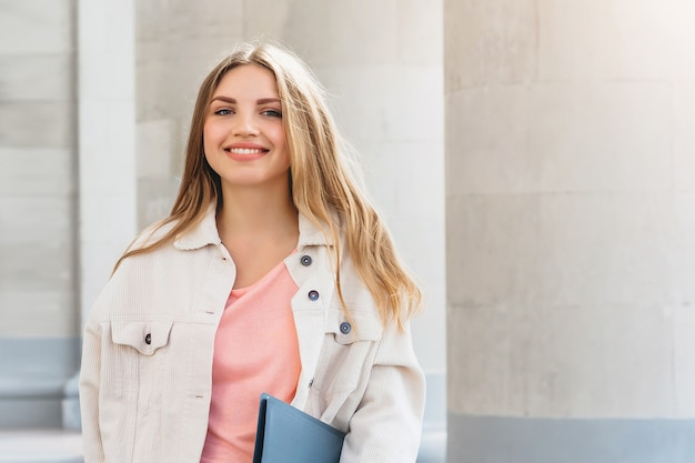 Estudiante rubia joven que sonríe contra universidad.