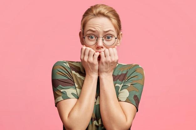 Estudiante rubia nerviosa se muerde las uñas como preocupaciones antes de aprobar el examen, ha frustrado la mirada a la cámara, se olvida de toda la información necesaria, posa contra el estudio rosa