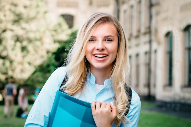 Una estudiante rubia está sonriendo y sosteniendo libros y un cuaderno en sus manos sobre un fondo universitario