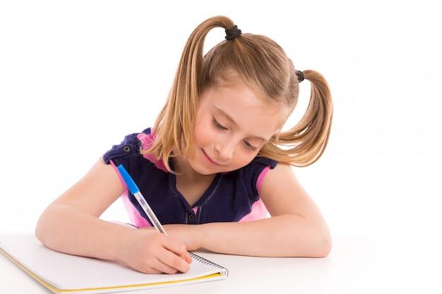 Estudiante rubio de la muchacha del niño con el cuaderno espiral en escritorio