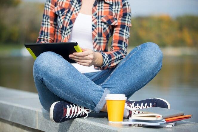 Estudiante sentado turco en el puente con la tableta