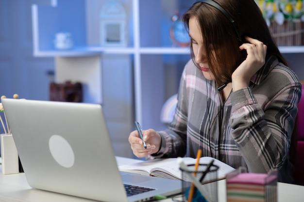 La estudiante seria usa auriculares en línea, estudia en línea con un maestro de internet, aprende un idioma hablando mirando la computadora portátil, una mujer joven enfocada hace una videollamada tutoría escribe notas
