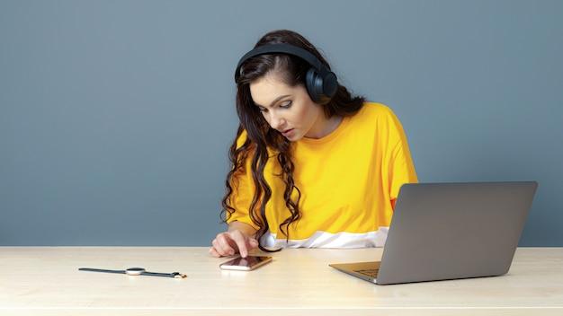 El estudiante se sienta con un auricular en la computadora, viendo y escuchando videos tutoriales en línea.